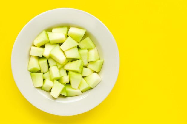 Cantaloupe meloen in plaat op gele achtergrond.