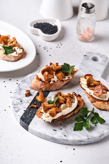 Cantharelsandwiches met kaas. open sandwich met romige kaas, kruiden en peper en verse peterselie op een oude houten achtergrond. bespotten. bovenaanzicht.