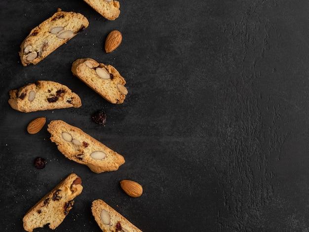 Cantucci (italiaanse dubbelgebakken koekjes, biscotti) met sinaasappelschil, amandelnoten en gedroogde cranberry .. vlakke lay-out, bovenaanzicht, plaats voor tekst. donkere achtergrond.