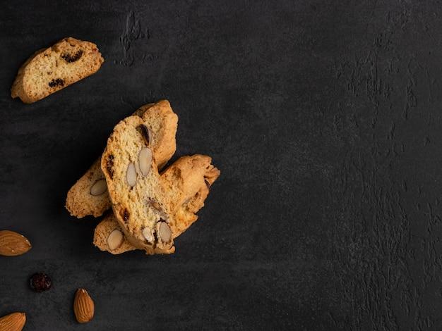 Cantucci (italiaanse dubbelgebakken koekjes, biscotti) met sinaasappelschil, amandelnoten en gedroogde cranberry .. vlakke lay-out, bovenaanzicht, plaats voor tekst. donkere achtergrond. Premium Foto
