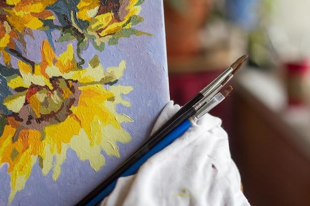 Canvas, verf, penselen, paletmes liggend op de tafel.