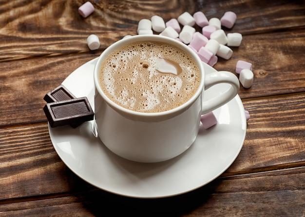 Cap van koffie op kleine plaat met twee kleine chocolade en marshmallow op tafel.