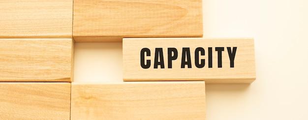 Capaciteit tekst op een strook hout liggend op een witte tafel. concept.