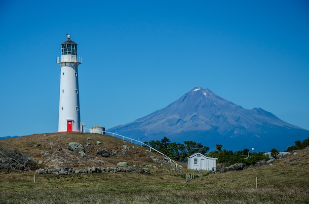 Cape egmont lighthouse met de berg taranaki erachter in pungarehu, nieuw-zeeland