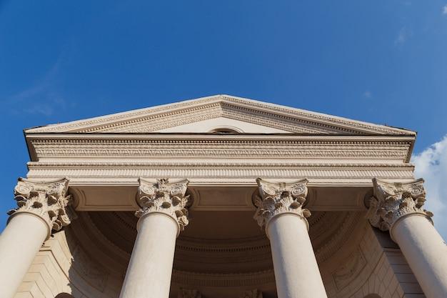 Capitoolvoorgevel met kolommen op blauwe hemelachtergrond. onderaanzicht