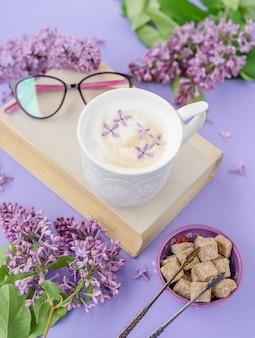 Cappuccino, boek met glazen en violet lila bloemen