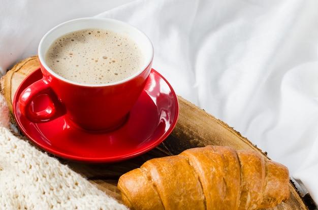 Cappuccino, chocolade en croissant op een bed.