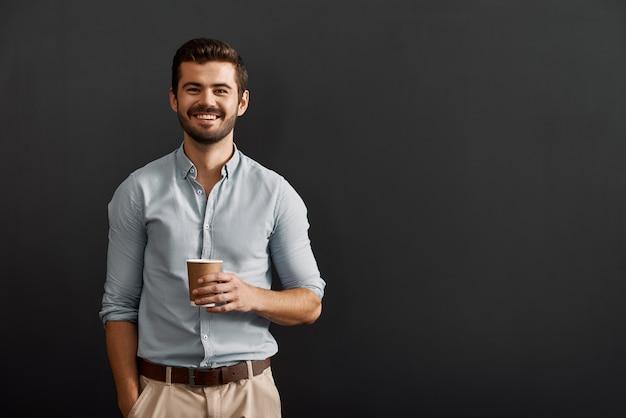 Cappuccino drinken vrolijke jonge bebaarde man met een kop warme koffie en kijken naar