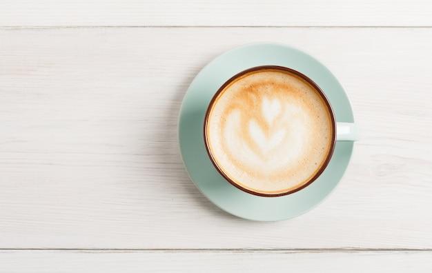 Cappuccino in blauwe koffiekopje bovenaanzicht close-up op wit hout.