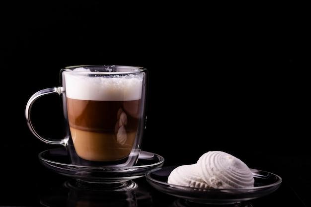 Cappuccino in een glazen kop en marshmallows op een transparante schotel.