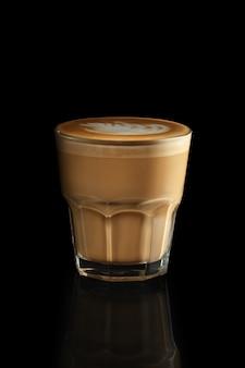 Cappuccino in rotsenglas dat op zwarte wordt geïsoleerd