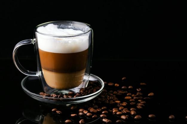 Cappuccino-koffie in een transparante kop op een zwarte achtergrond en verspreide koffiebonen.