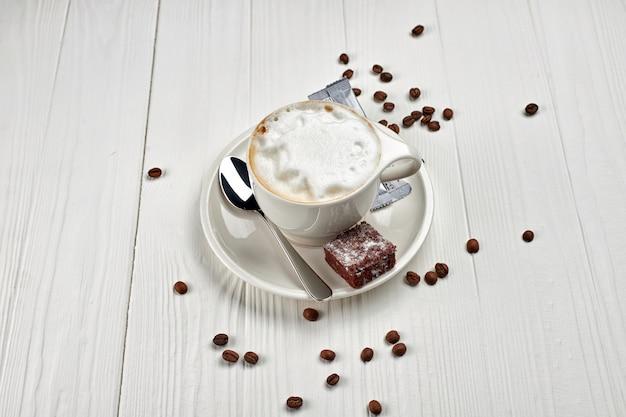 Cappuccino, koffie met melk, met een fluitje van een cent, in een witte kop, op een wit houten bord, met koffiebonen verspreid
