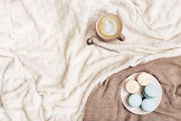 Cappuccino-koffiekunst in kop en zoete bitterkoekjes op huistafel met gebreide stof