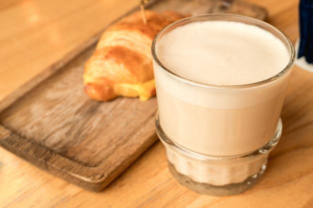 Cappuccino met een zacht schuim in een transparant glas en verse croissants op een houten dienblad