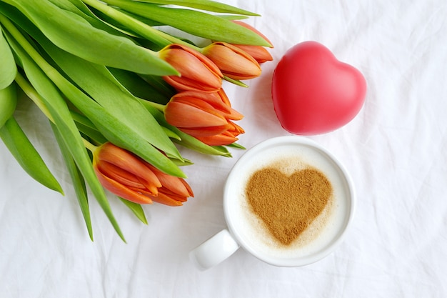 Cappuccino met hart van kaneel en bloemensamenstellingstulpen, de lenteconcept van de valentijnskaartendag