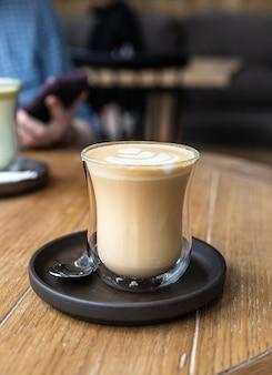 Cappuccino met latte art in glazen beker op houten tafel in café of koffiehuis