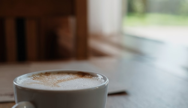Cappuccino of koffie latte op een houten tafel. close-up, selectieve focus, zonlicht uit het raam. koffiepauze idee, koffiepauze