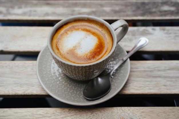 Cappuccino of latte met schuimend schuim, grijze hoogste de meningsclose-up van de koffiekop die op houten lijst wordt geïsoleerd. café en bar, barista kunstconcept.