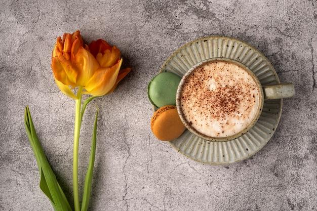 Cappuccinokoffie in een kop op een schotel met bitterkoekjes en gele tulp op een grijze betonnen tafel, ontbijtconcept, close-up, kopie ruimte
