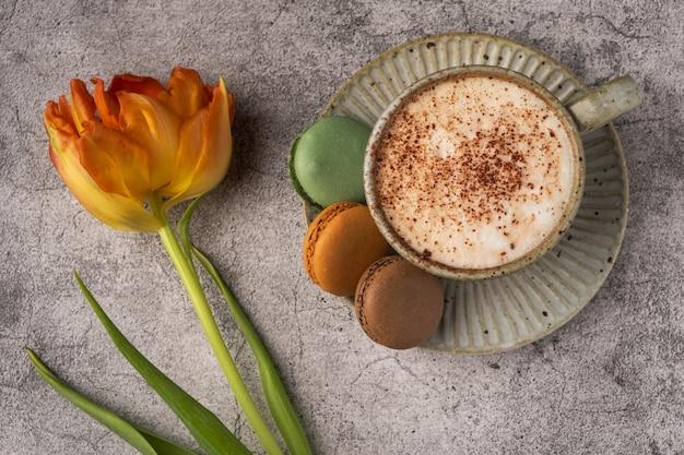 Cappuccinokoffie in een kop op een schotel met makarons en gele tulp op een grijze concrete lijst