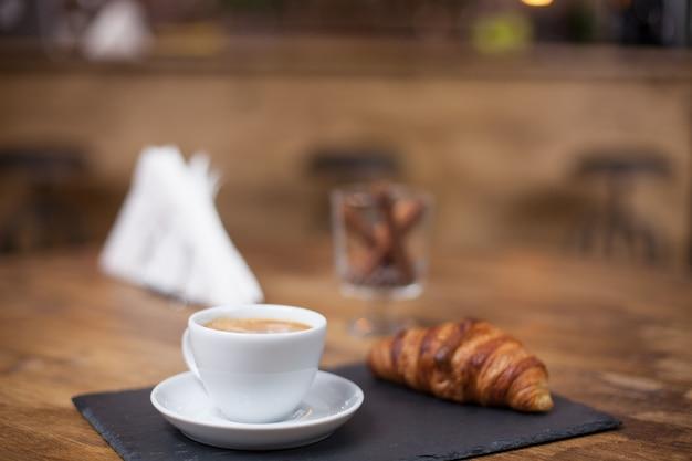 Cappuccinokoffie in een witte kop op een houten tafel naast een heerlijke croissant. lekkere slang. uitstekende koffiewinkel.