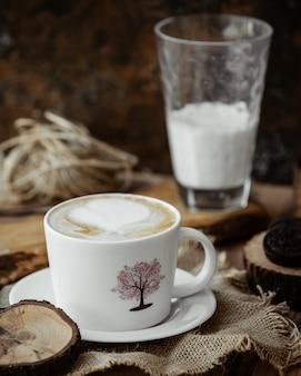 Cappuccinokop en glas melk op de lijst