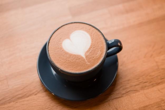 Cappuccinokop in het café op een houten tafel