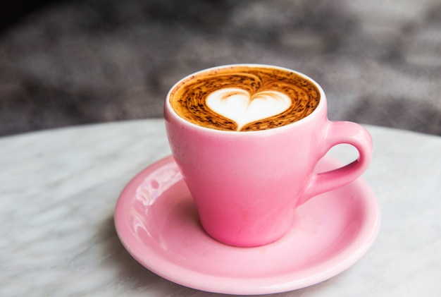 Cappuccinokop met hart latte kunst op marmeren lijstachtergrond.