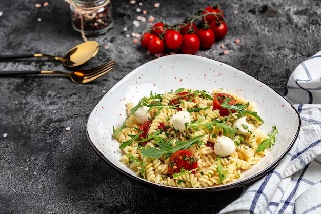 Caprese salade fusilli pasta met cherrytomaatjes en mozzarella kaas. banner, menu recept plaats voor tekst, bovenaanzicht.