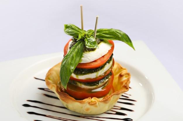 Caprese salade, italiaanse salade. plakjes tomaat en verse mozzarella en basilicumbladeren met olijfolie.