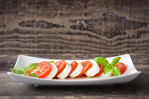 Capresesalade met de tomaten van de mozarellakaas en basilicum op rustieke houten lijst