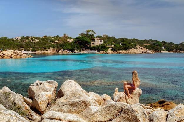 Capriccioli-strand in costa smeralda sardinië italië blond meisje zittend op de rots en genietend van het schilderachtige uitzicht op de kustlijn en de kristalheldere azuurblauwe zee vakantie op sardinië