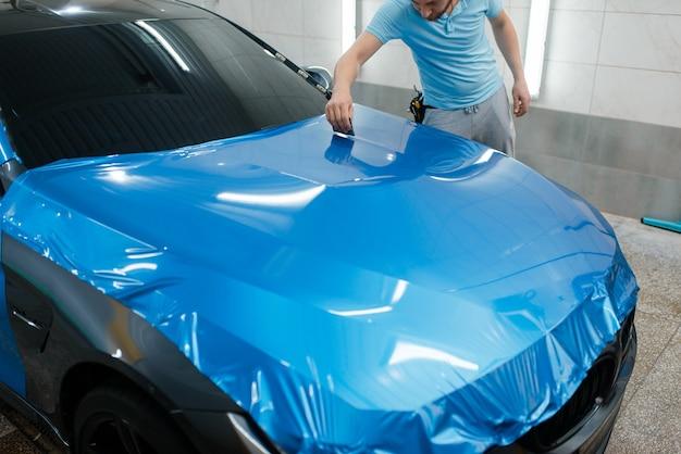 Car wrapping, man met zuigmond installeert beschermende vinylfolie of film op motorkap. werknemer maakt automatische detaillering. autolakbeschermingscoating, professionele afstemming