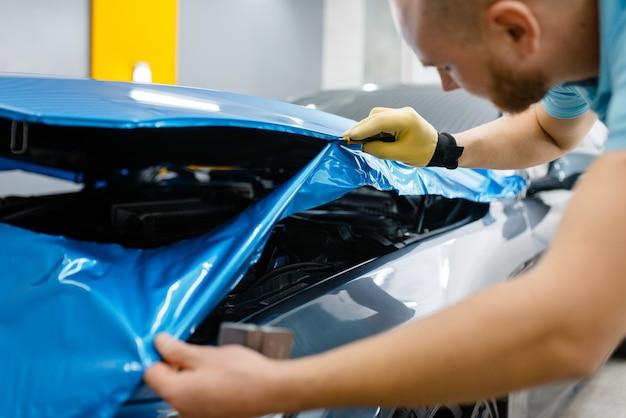 Car wrapping, man snijdt vinyl beschermfolie of film op de motorkap close-up. werknemer maakt automatische detaillering. autolakbeschermingscoating, professionele afstemming