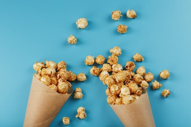 Caramel popcorn in een papieren envelop op een blauwe achtergrond.