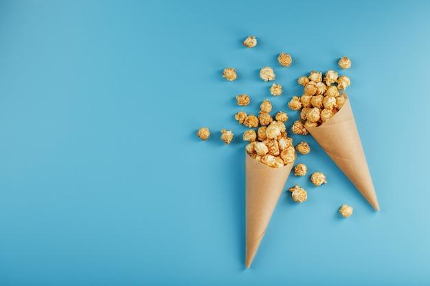 Caramel popcorn in een papieren envelop op een blauwe ondergrond. heerlijke lof voor het kijken naar filmfilms, series, cartoons. vrije ruimte, close-up. minimalistisch concept.