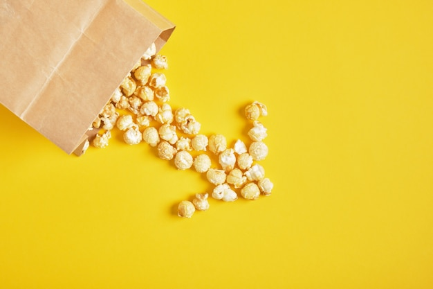 Caramel popcorn in een papieren zak op gele achtergrond