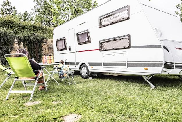 Caravan midden in de natuur met tafels en stoelen