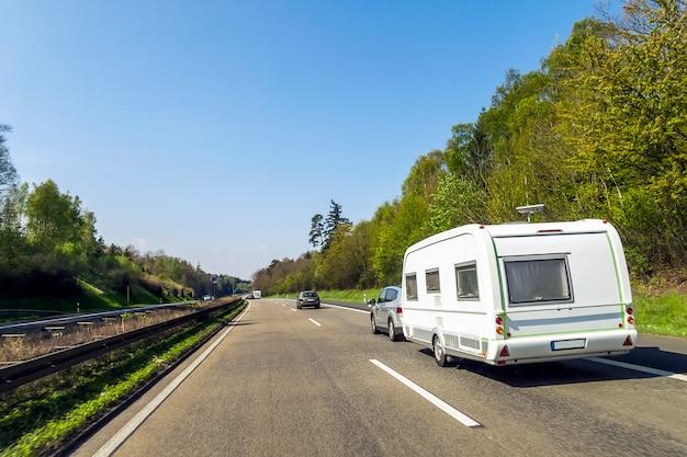 Caravan of recreatieve voertuig camper aanhangwagen op een snelweg weg