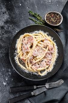 Carbonara pasta, bucatini met pancetta, ei, parmezaanse kaas en roomsaus. bovenaanzicht