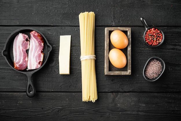 Carbonara pasta ingrediënten ingesteld, op zwart houten, bovenaanzicht plat lag