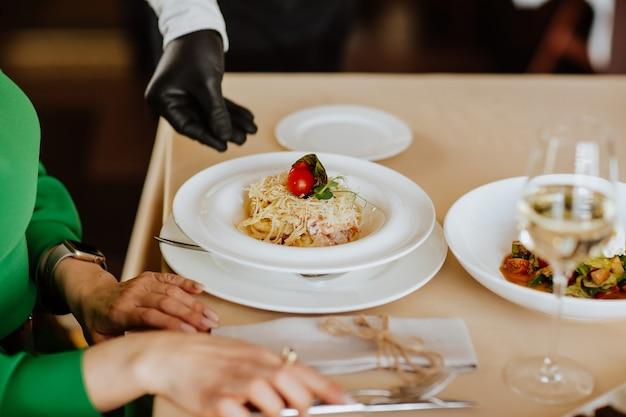 Carbonara pasta met spek, kaas en room serveren in restaurant. focus ligt op de pasta.