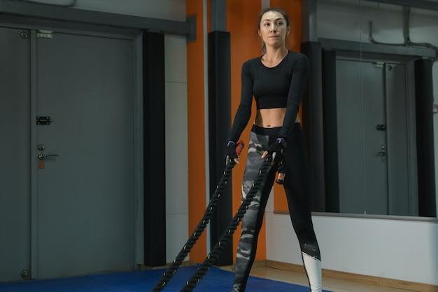 Cardio triage mooie vrouw bezig met touwen in de sportschool