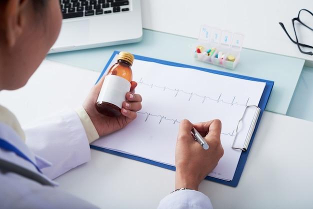 Cardioloog die cardiogram van zieke patiënt analyseert en fles medicijnen voorschrijft