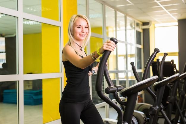 Cardiotraining in de sportschool door mooie vrouw