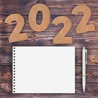 Cardstock numbers 2022 happy new year sign in de buurt van white spiral paper cover notebook met pen over houten tafel achtergrond. 3d-rendering