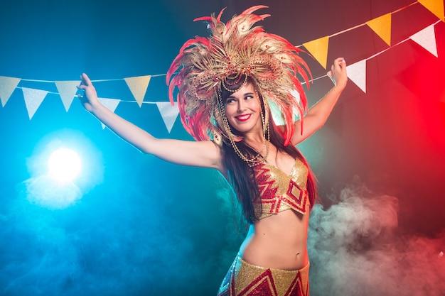 Carnaval, buikdans en vakantieconcept - mooie sambadanseres die gouden kostuum draagt en