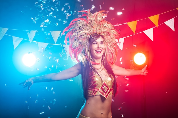 Carnaval, danseres en vakantieconcept - portret van een sexy vrouw in een kleurrijk weelderig kostuum van carnavalveren. nachtleven van danseres.