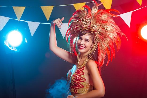 Carnaval, danseres en vakantieconcept - schoonheid brunette vrouw in cabaret pak en hoofdtooi met
